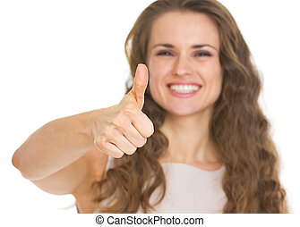Closeup on young woman showing thumbs up