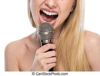 Closeup on young woman singing with microphone