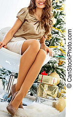 Closeup on young woman sitting near christmas tree