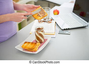 Closeup on young woman spread toast with chocolate cream