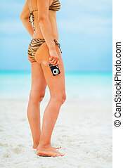 Closeup on young woman standing on beach with photo camera