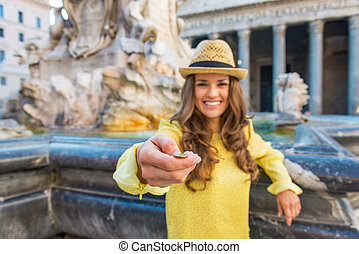 Closeup on young woman tossing coin near fountain of the...