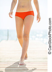 Closeup on young woman walking on bridge