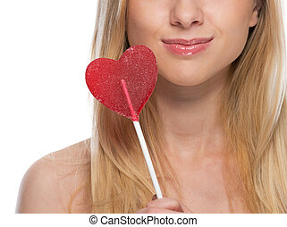 Closeup on young woman with heart shaped lollipop