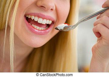 Closeup on young woman yogurt