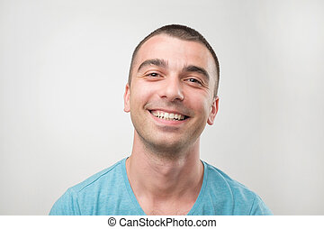 Closeup ortrait of smiling man in blue t-shirt.