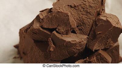 Closeup pan of chunks of gianduja hazelnut milk chocolate on paper, shallow focus