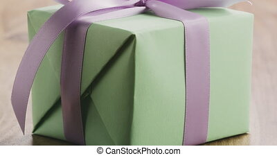 Closeup pan of green gift box with purple ribbon bow on old wood table
