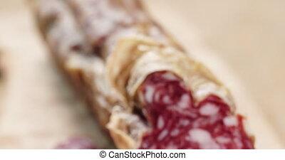 Closeup pan of sliced italian salame, shallow focus