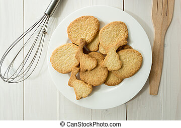 Closeup photo from above of dish with cookies and kitchen utensils on white desk