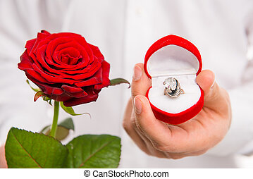 Closeup photo of a handsome man with a red rose and wedding ring