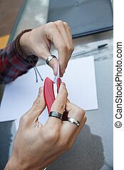 Closeup photo of a person stapling documents with a stapler on a table.