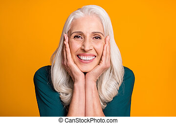 Closeup photo of amazing cheerful white haired grandma aged lady toothy smiling, overjoyed arms on cheeks affectionate wear green shirt isolated vibrant yellow background