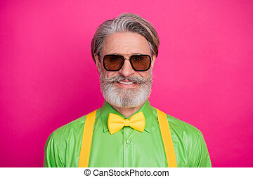 Closeup photo of amazing trendy clothes grandpa positive facial expression good mood wear sun specs green shirt yellow suspenders bow tie isolated vivid pink color background