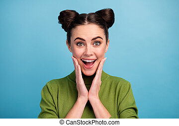 Closeup photo of attractive brunette lady two funny buns good mood open mouth arms on cheeks wear warm green turtleneck pullover isolated blue color background
