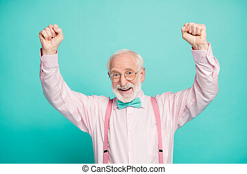 Closeup photo of attractive crazy excited grandpa raise fists up celebrating money income wear specs pink shirt suspenders bow tie isolated teal color background