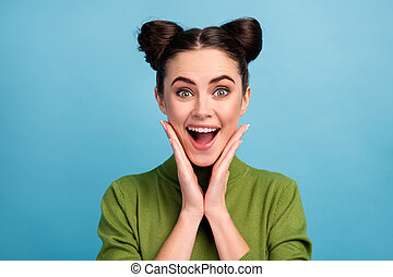Closeup photo of attractive crazy lady two funny buns good mood open mouth arms on cheeks wear warm green turtleneck pullover isolated blue color background