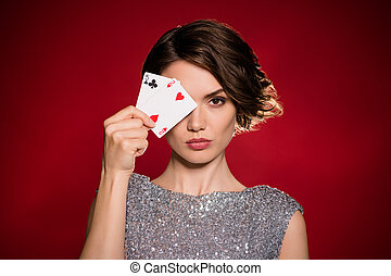 Closeup photo of attractive lady professional casino player hiding eye hold two deck play cards bet risky clever gamer all in wear shine dress isolated dark red gradient color background