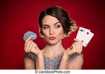 Closeup photo of attractive lady professional casino player hold chips two deck play cards bet risky think over next clever move wear shine dress isolated dark red gradient color background