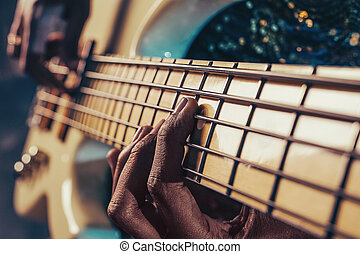 Closeup photo of bass guitar player hands