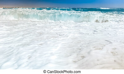 Closeup photo of beautiful sea waves breaking on shore. Wet sand and water splashes on the beach