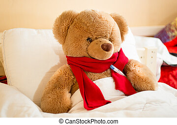 brown teddy bear in read scarf lying in bed with thermometer...