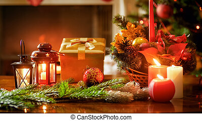 Closeup photo of burning candles, gift box and Christmas wreath on wooden table
