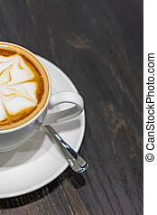 Closeup photo of cappuccino latte art coffee on rustic background