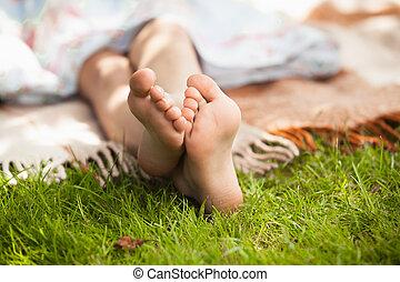 child feet on green grass