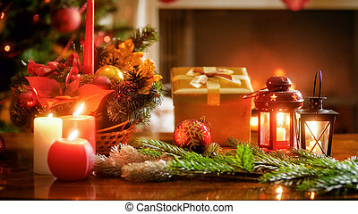 Closeup photo of Christmas decorationg on wooden table in living room against burning fireplace