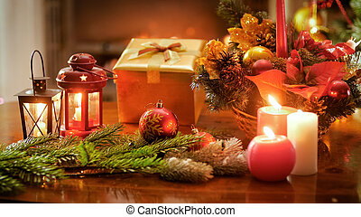 Closeup photo of Christmas wreath, burning candles and gift box on wooden table
