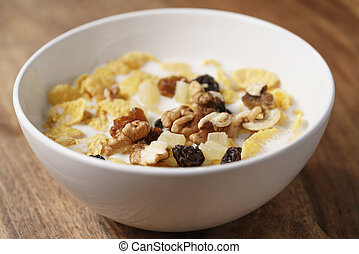closeup photo of corn flakes with fruits and nuts in white bowl on wood table