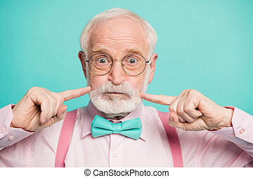 Closeup photo of crazy funky grandpa press fingers on cheeks big eyes no emotions wear specs pink shirt suspenders bow tie isolated bright teal color background