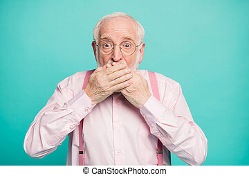 Closeup photo of crazy grandpa hiding mouth lips don't speak keeping silence big fear eyes wear specs pink shirt suspenders bow tie isolated bright teal color background