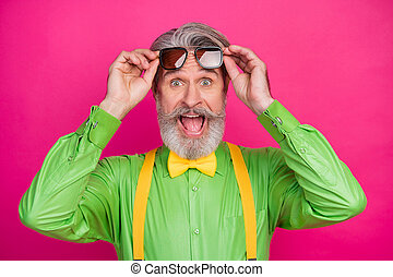 Closeup photo of crazy trendy clothes aged grandpa positive news good mood sale shopping wear sun specs green shirt yellow suspenders bow tie isolated vivid pink color background
