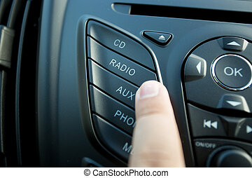 Closeup photo of driver pushing radio button on dashboard