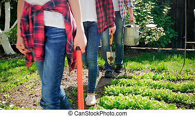Closeup photo of family holding gardening tools walking at backyard garden