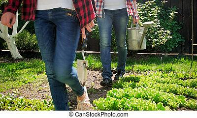 Closeup photo of family walking at backyard garden with gardening tools