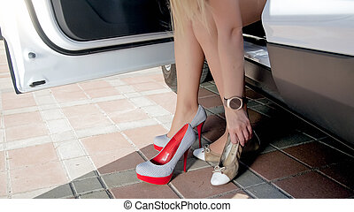 Closeup photo of female driver changing comfortable shoes to high heels