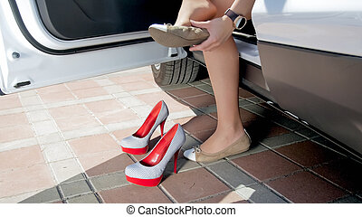 Closeup photo of female driver changing shoes after driving a car