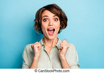 Closeup photo of funny excited lady raise fists screaming loudly celebrating money lottery winning wealthy rich person wear casual green shirt isolated blue color background