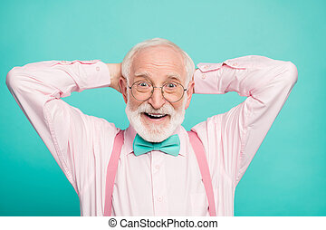 Closeup photo of funny grandpa positive cheerful facial expression good mood arms behind head wear specs stylish pink shirt suspenders bow tie isolated teal color background