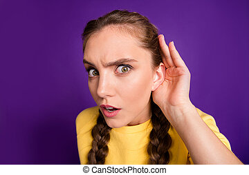 Closeup photo of funny lady long braids holding arm near ear listening, fresh rumours chatterbox person wear casual yellow jumper isolated purple color background