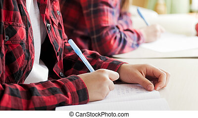 Closeup photo of girls hand writing exercise in copybook