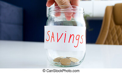 Closeup photo of hand throwing coins in glass jar for savings