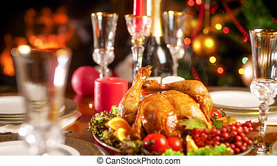 Closeup photo of hot baked chicken on festive table against Christmas tree and fireplace