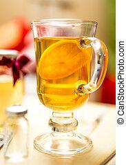 Closeup photo of hot tea with lemon in transparent glass -...