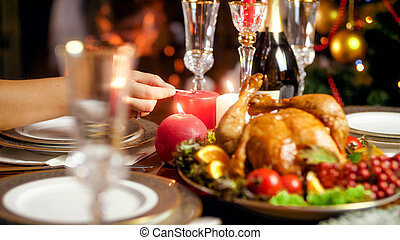 Closeup photo of lighting up candles on Christmas dinner table against burning fireplace