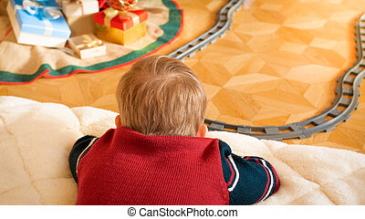 Closeup photo of little boy lying on floor and looking at his toy train riding on railways at living room