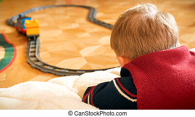 Closeup photo of little boy watching his toy train riding on railways on wooden floor at house